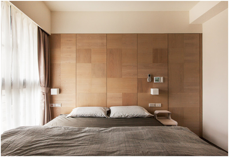The bedroom does have one small, slim nightstand on the right, but otherwise the room has minimal furniture. A large window with airy curtains is on the left wall.