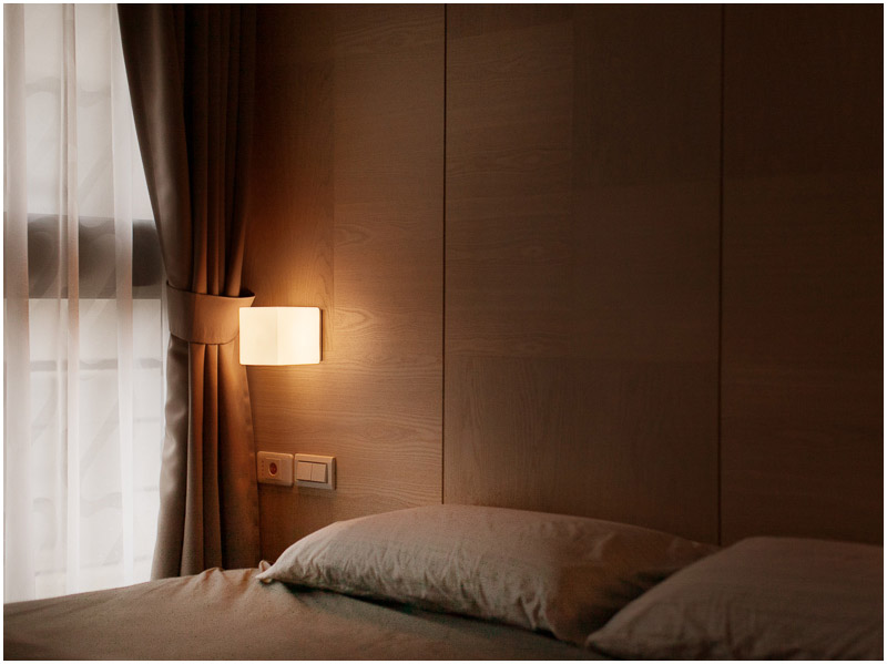 The oak accent wall behind the bed has built-in storage and small cube lights instead of nightstands and lamps.
