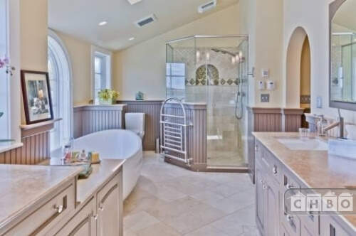 The recently renovated primary bathroom includes a spacious shower enclosure with a towel rack on the side, a large soaking tub in front of one of the windows, archways and several vanities.