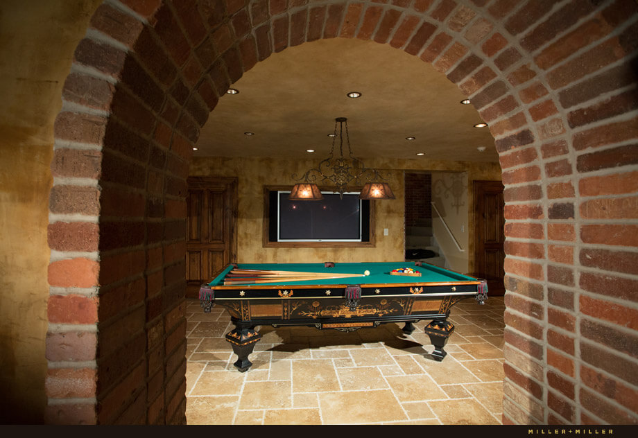 antique-billiards-table-European-style-basement The basement returns to a mediterranean feel with a brick archway leading into the main room. A large, ornate billiards table sits in the very center of the room, with a television on the wall behind it.