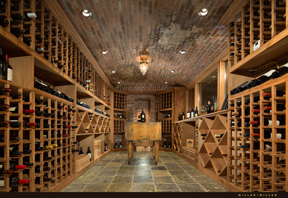 The enormous wine cellar has hundreds of shelves for wine and a tasting table in the center.