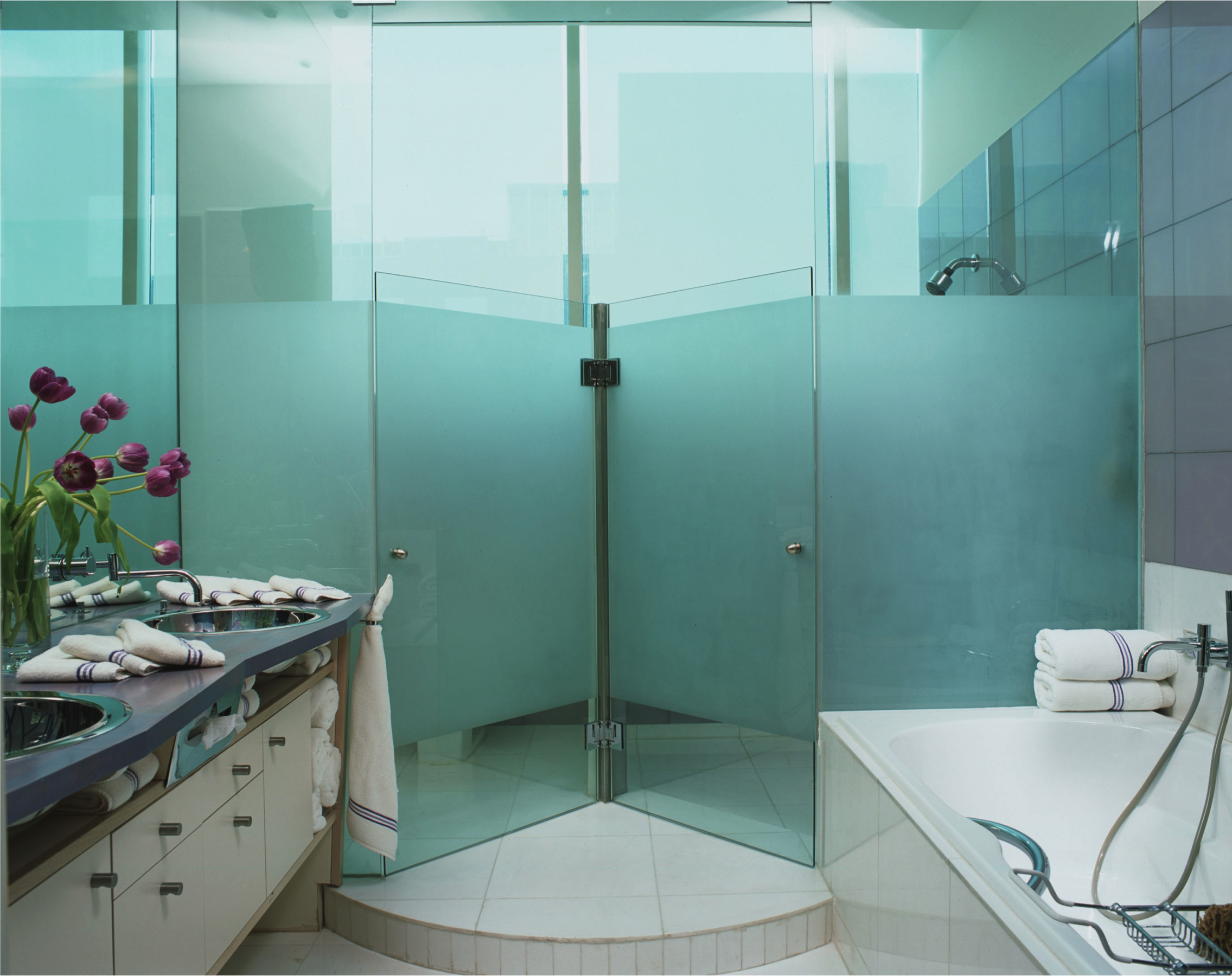 Another bathroom has dual showers enclosed in frosted glass. The soaking tub has purple striped towels that match the purple counters.