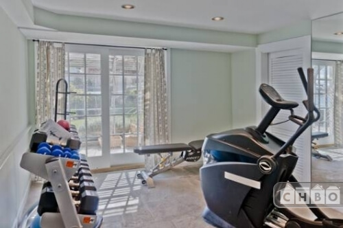 The exercise room on the ground floor has plenty of equipment and soft green pastel walls.
