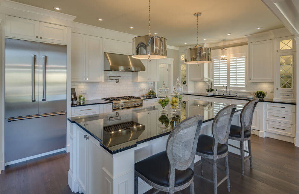 From this angle, we can see the white backsplash in the sink and cooking areas. Glass-front cabinets on either side of the far wall add visual interest.