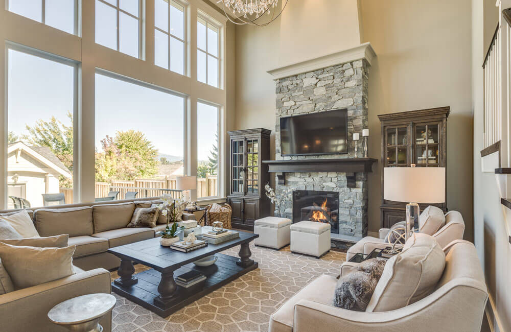 The coffered ceiling of the dining room erupts into a soaring cathedral ceiling in the living room. Ample seating consists of a L-shaped couch, two chairs, and two ottomans. Natural light is let in through the floor-to-ceiling windows.
