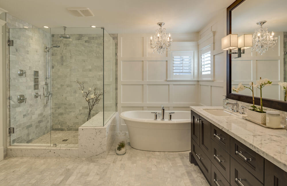 The primary bathroom has a large stone and tile glass-enclosed shower stall, complete with a bench. A small chandelier hangs above the large soaking tub. The dark-wood vanity is topped with marble.