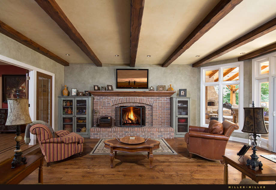 The focal point of this room is the screened brick fireplace and rustic exposed wood beam ceiling. Through the white trimmed windows the backyard patio is visible. Glass doors to the patio allow the party to move outdoors easily.