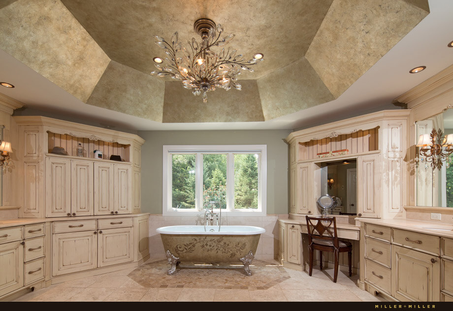The adjoining primary bathroom has a gorgeous crystal chandelier hanging from the vaulted ceiling. Around the perimeter of the room are built-in cabinets, vanities, makeup tables and towel storage.