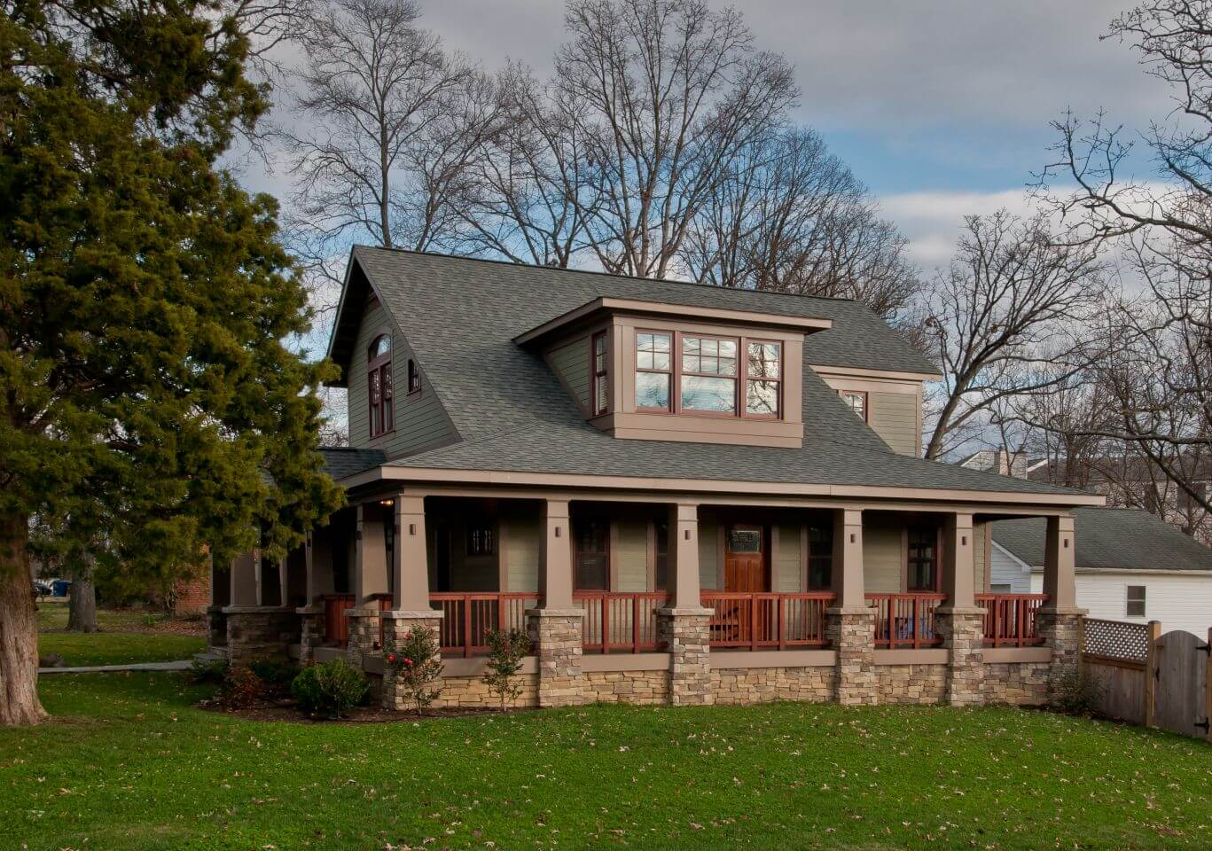 A shot from the side of the home, featuring the gorgeous wraparound porch and providing a peek into the fenced-in backyard.