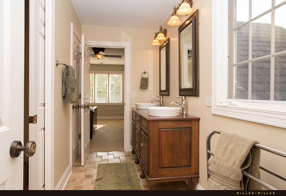 A second Jack-and-Jill bathroom has heated floors and vessel sinks. The long and narrow bathroom is shared between the two bedrooms.