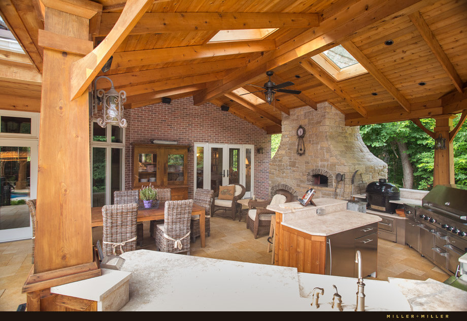 The outdoor kitchen has a ton of countertop space, a small island, grill, stove, sink and even a stone pizza oven.