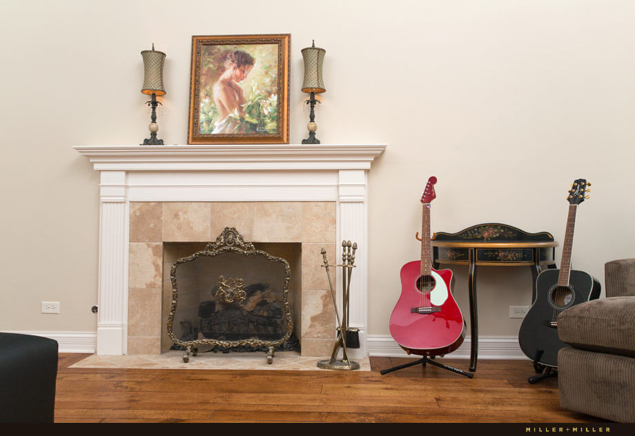 A wood-burning fireplace with an ornate screen is flanked by a black table with floral details. Guitars add a personal and modern touch to the traditionally styled room.