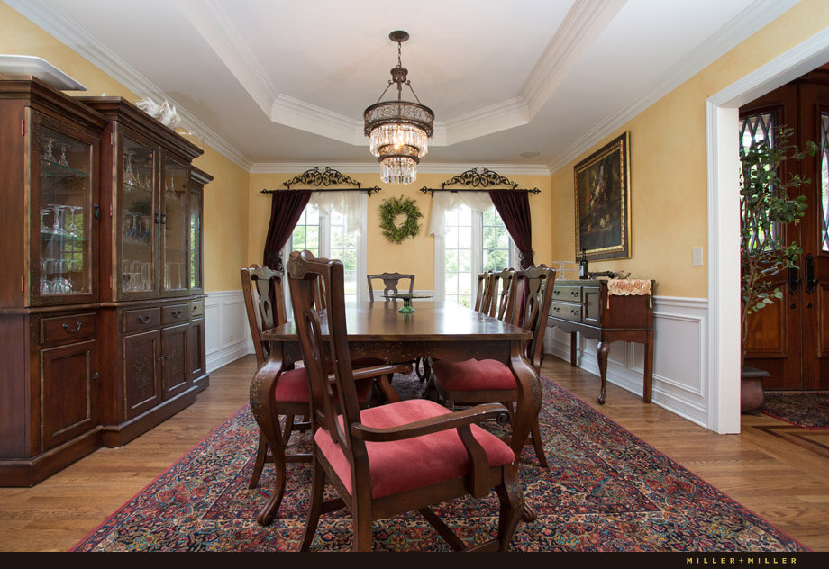 The formal dining room connects to both the large kitchen and to the entryway. An ornate rug with reds, blues and greens complements the velvet seated chairs and rich dark wood furniture.