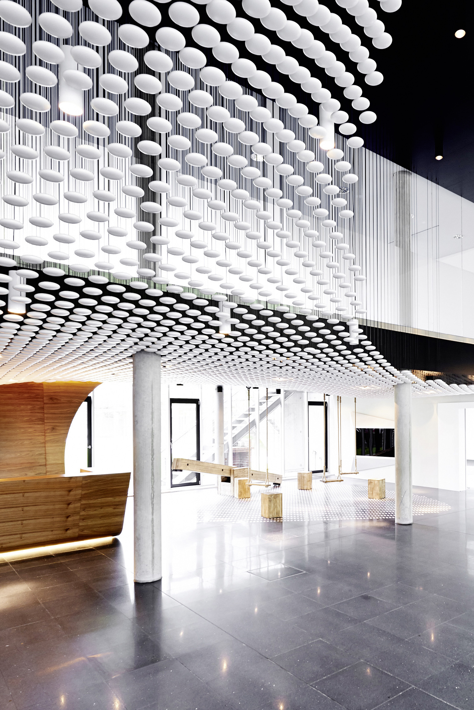 The brightly lit entrance stands natural wood in sharp contrast with dark tiled flooring and exposed concrete columns, below the clouds of white spheres.