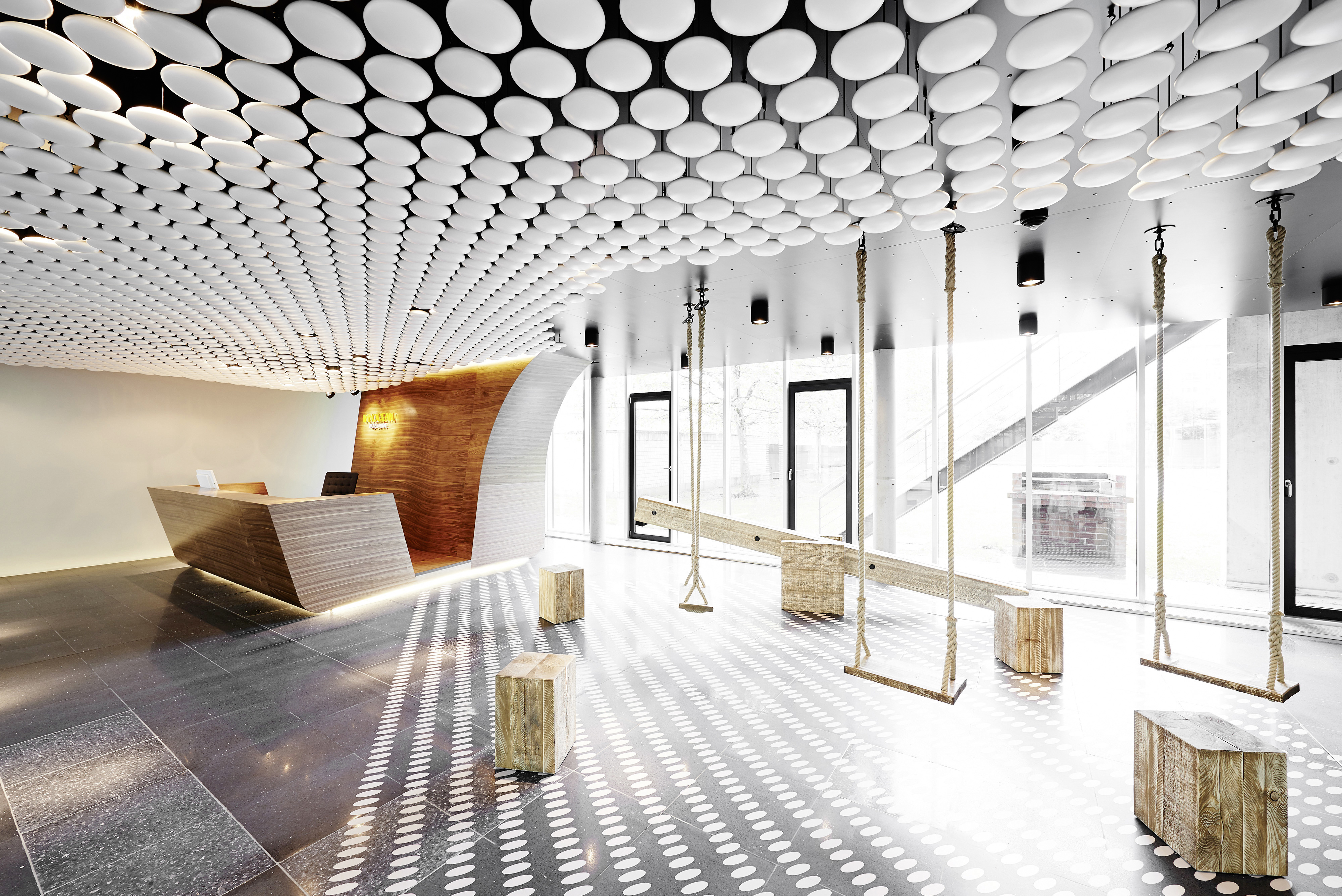 As seen on our top image, the welcoming area floats a stream of white spheres over a minimalist, almost whimsical space featuring dramatically carved wood desk and a series of swings and wood blocks.
