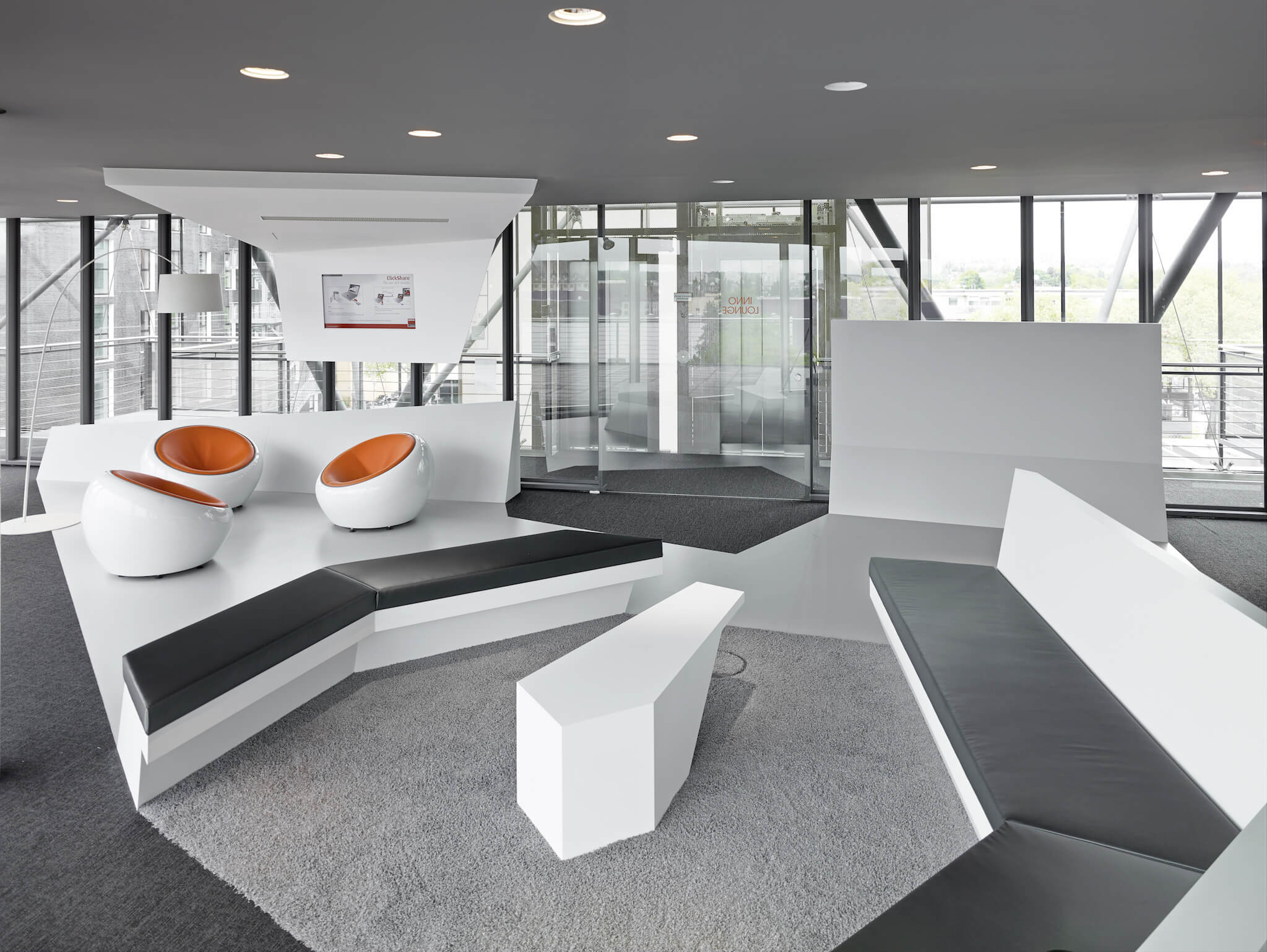 Polygonal constructions abound in the office, seen here functioning as the framing shell to a conversational space. Minimalist, high contrast philosophy informs the design, pairing black leather cushions with white geometric structures, plus bold orange standing out on the egg chairs.