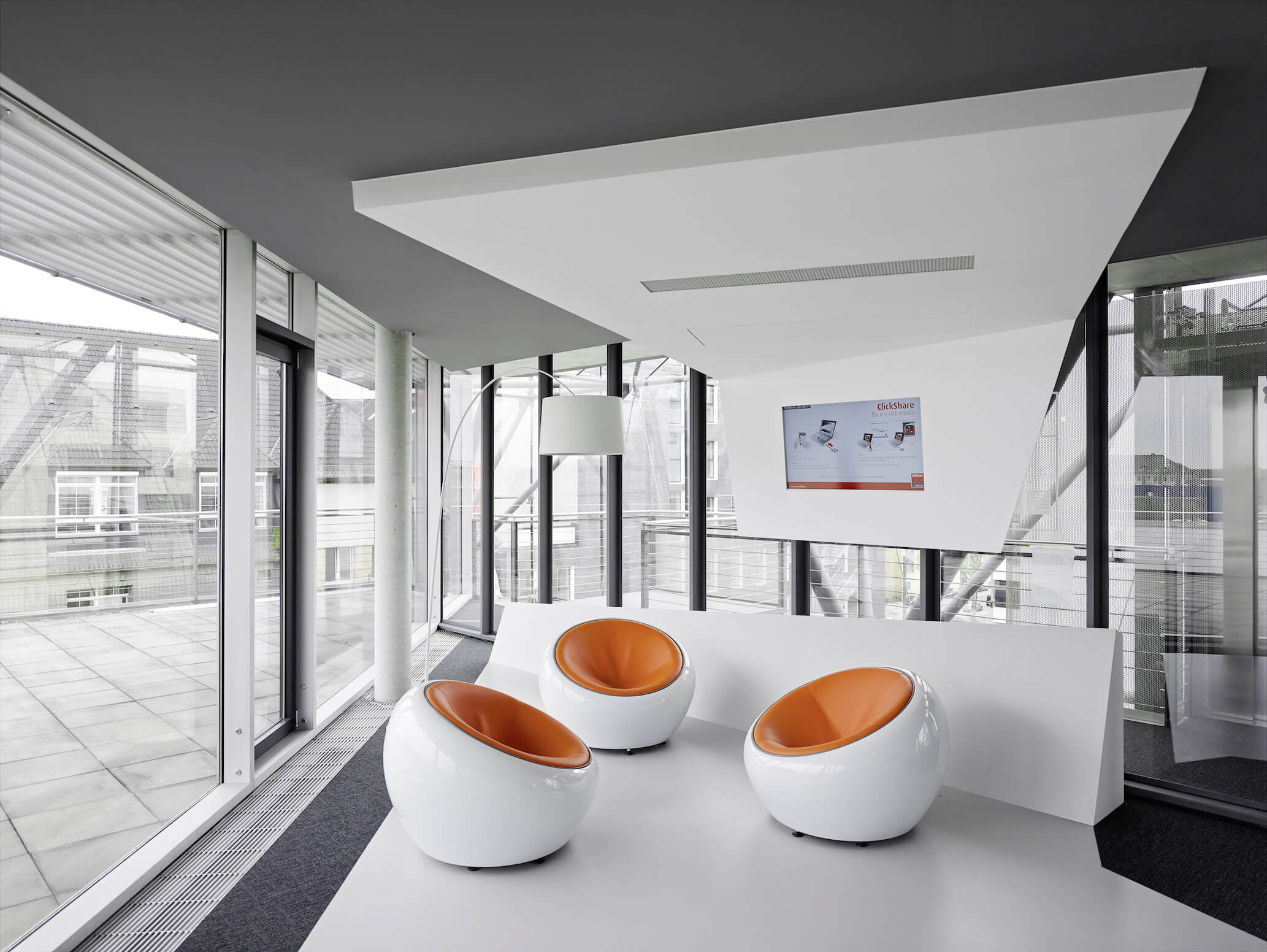 """Here we have a closer view of the trio of """"egg"""" chairs with orange leather seating. Full height glass surrounds the space, lending natural light and an expansive, minimalist feeling."""