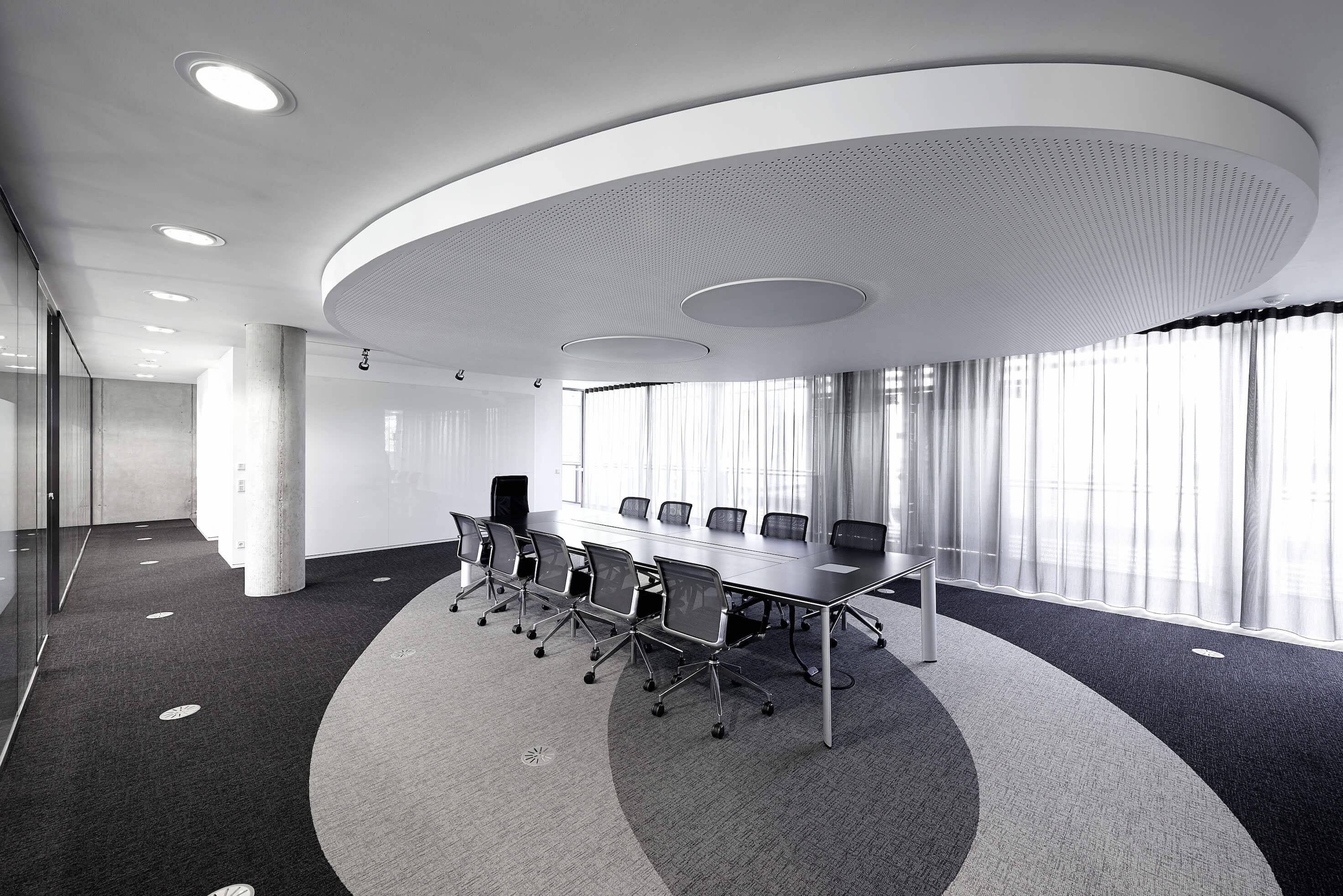 Here we see a large, open conference room with lengthy black and metal textured table standing beneath an oval ceiling detail, mirrored on the carpet design. Again, floor to ceiling glass panels wrap the space, here seen with curtains for privacy and shade.