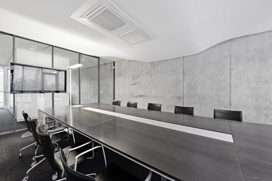 Throughout the office, bare concrete pairs with stark white and black tones, for a muted look. Large swaths of glass allow for an open, breathable look.