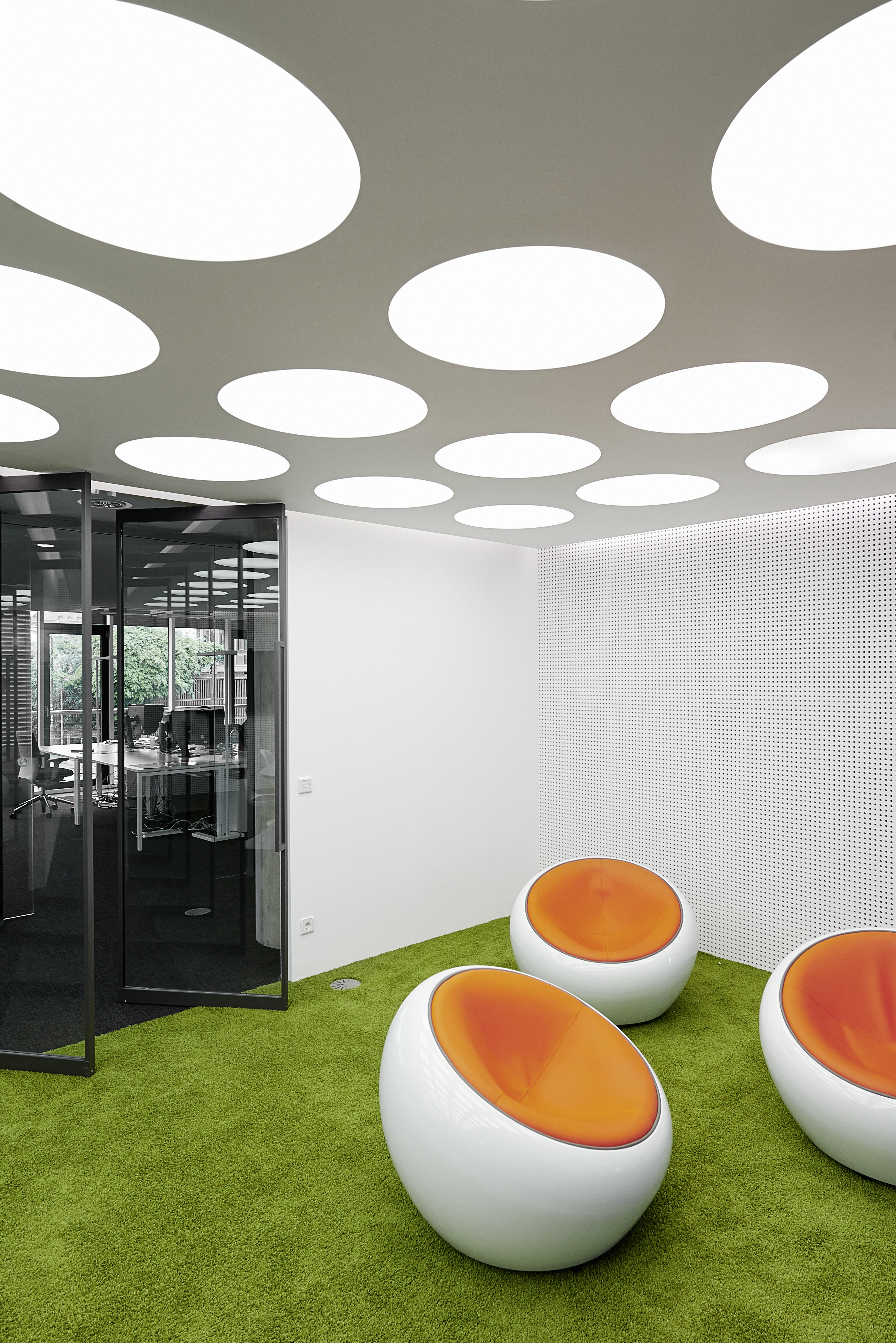Beneath large circle lighting cutouts in the ceiling, we see another trio of orange-cushion egg chairs on the putting green-like carpeting.