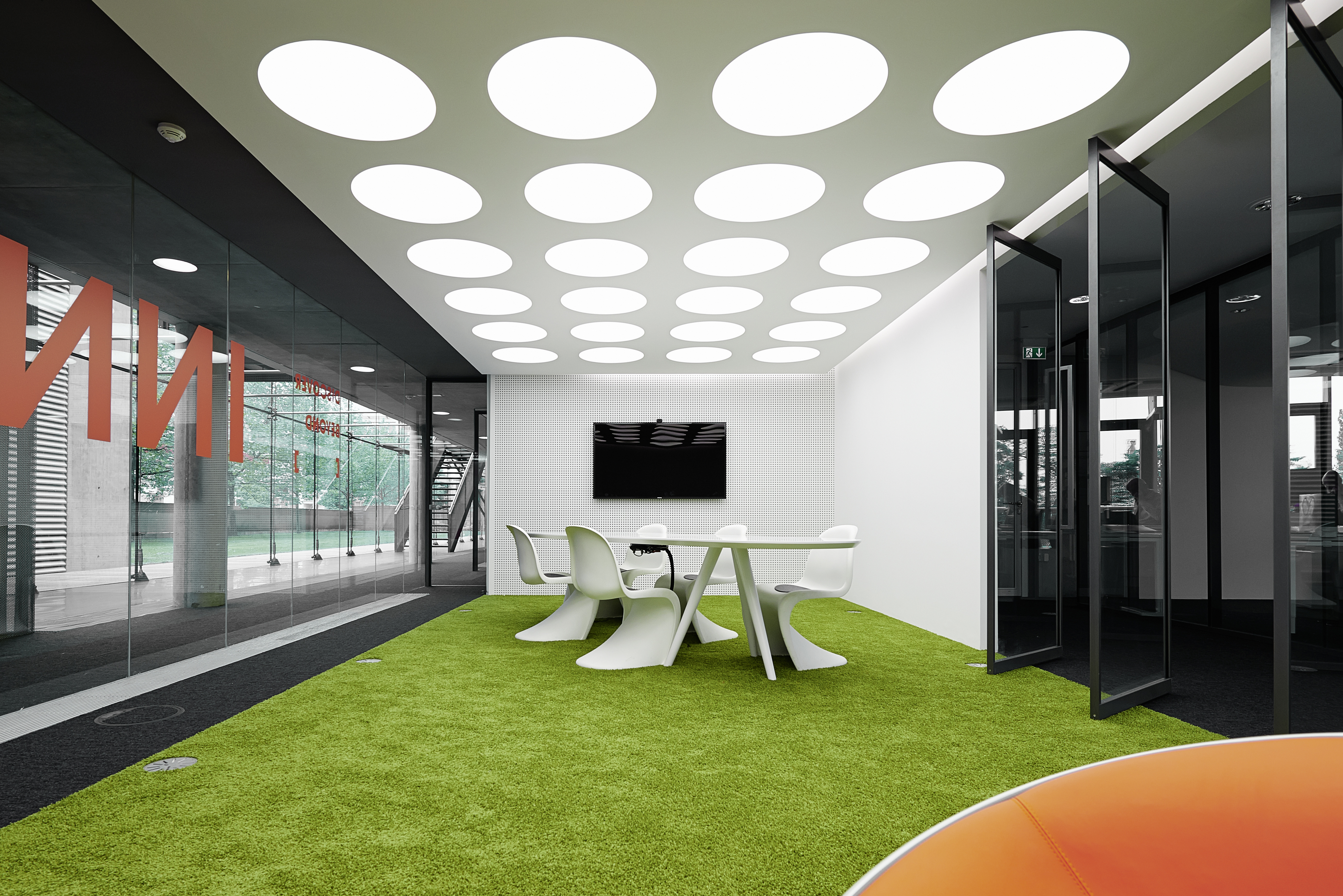From a wide angle, we see the brightly colored discrete conference space nestled between two expanses of neutral toned office, for a burst of color in the building.