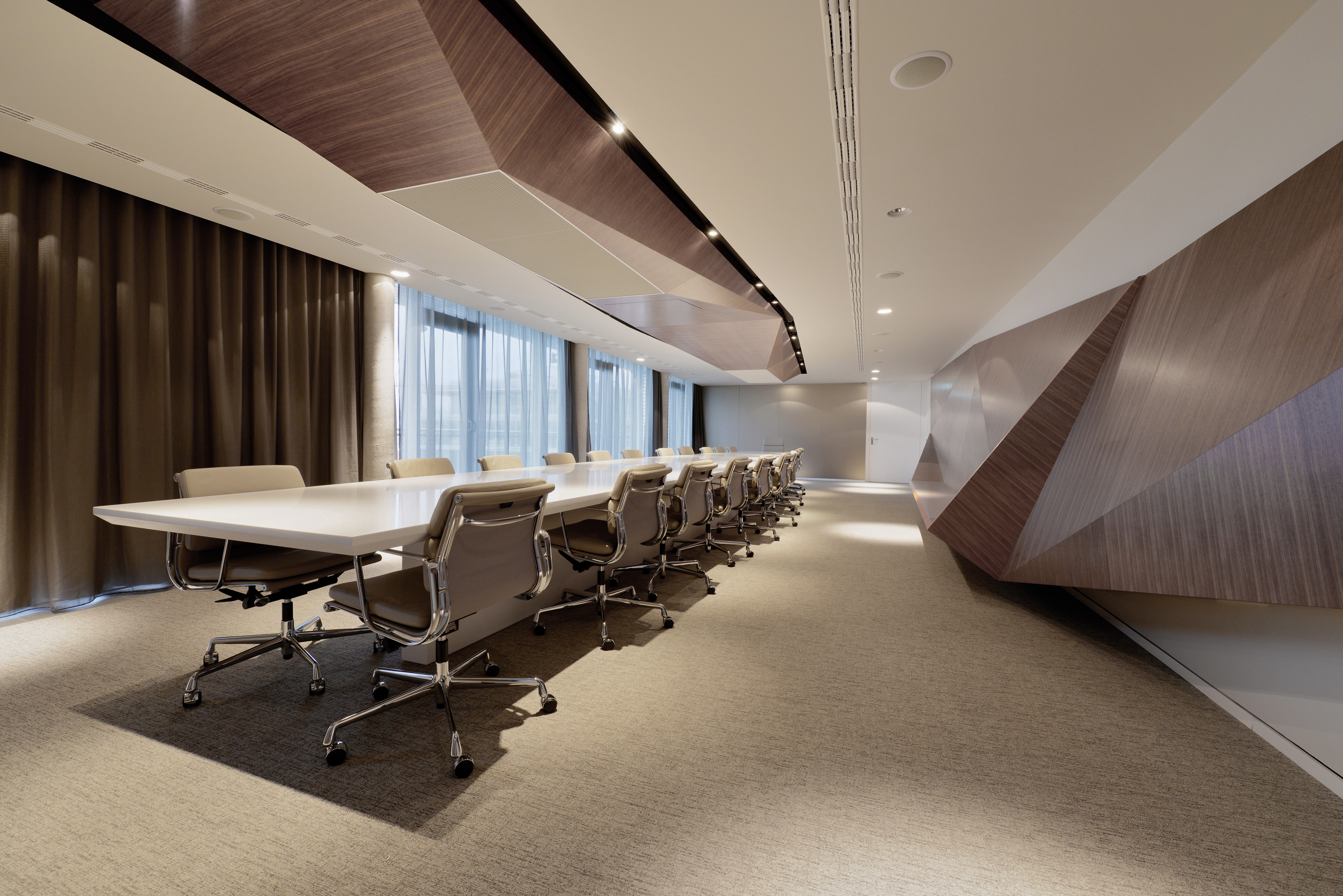 This expansive conference space showcases large form versions of the polygonal structures, in natural wood tones here. These geometric shapes break from the standard right angled form of an office, providing a unique yet sharply industrial creative element.