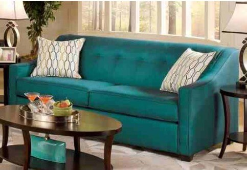 This more contemporary example is in a bright peacock blue. The backrest is one solid cushion with button-tufting. A higher backrest allows you to simply curl up in the corner.
