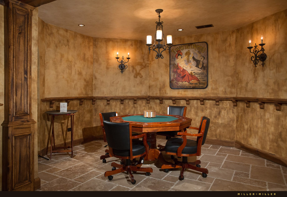 A small side room with textured walls and stone tile floors is host to a poker table with comfy black leather chairs.
