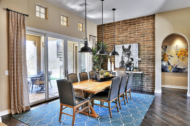 Traditional dining room with an adobe brick veneer wall beside the main archway entrance.