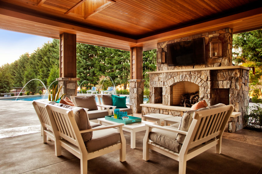 The covered outdoor patio has fantastic stone accents and an enormous stone fireplace with an open hearth. Peacock blue accents brighten up the beige cushions and light wood patio furniture.