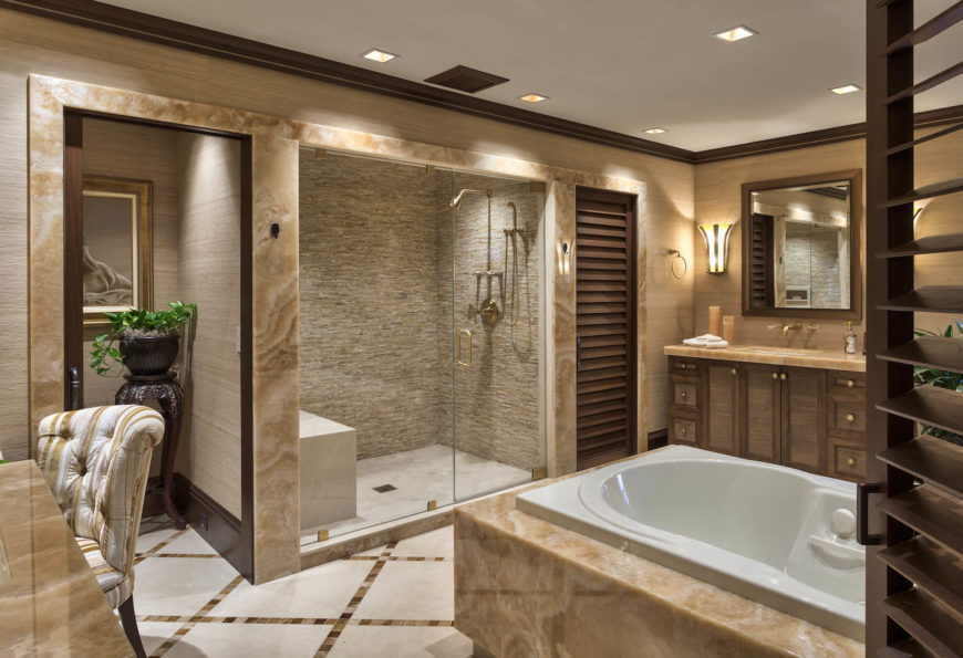 With a free standing soaking tub wrapped in marble at center, the bathroom holds dual vanities on each side, complemented by a pair of private commodes flanking the large glass enclosed shower.