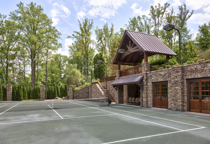 The grounds hold this extravagant tennis pavilion, with a full court surrounded by greenery, backed against a stone wall matching that of the home itself. With full sheltered viewing area and overhead spotlights, it has all the amenities of a professional court.