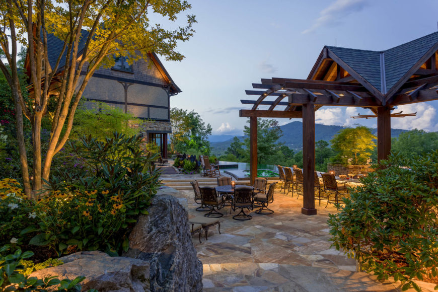 Moving back outdoors, we see the exterior dining space to the right, with stone crafted landscaping defining the path at left. Expansive mountain views are afforded throughout.
