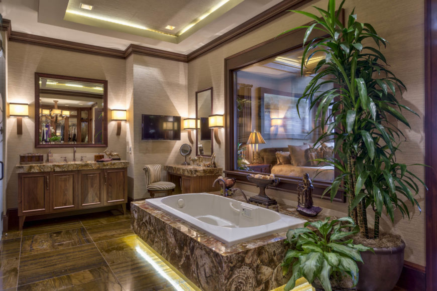 A large marble framed soaking tub sits below a window to the bedroom, with light emanating from beneath over the rich floor tiling. Thick slab countertops on the makeup station and vanity add a luxurious touch.