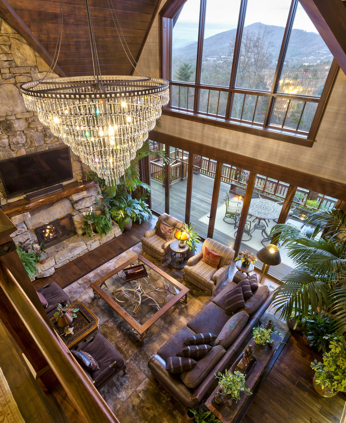 Moving indoors, we see the grand living room, packed with detailed furniture over rich hardwood flooring. The space is overlooked by a massive stone fireplace and two stories of windows, with retractible glass panels at ground level for balcony access.