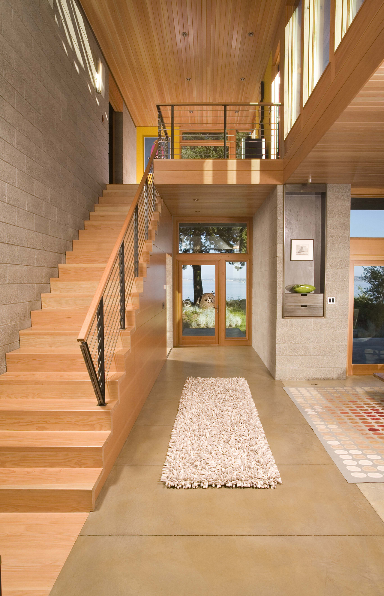 This lovely, warm entryway has a main living area to the right, a staircase to the left, and the short hallway straight ahead leads to the backyard. The entryway is a combination of warm wood and neutral stone tiles.