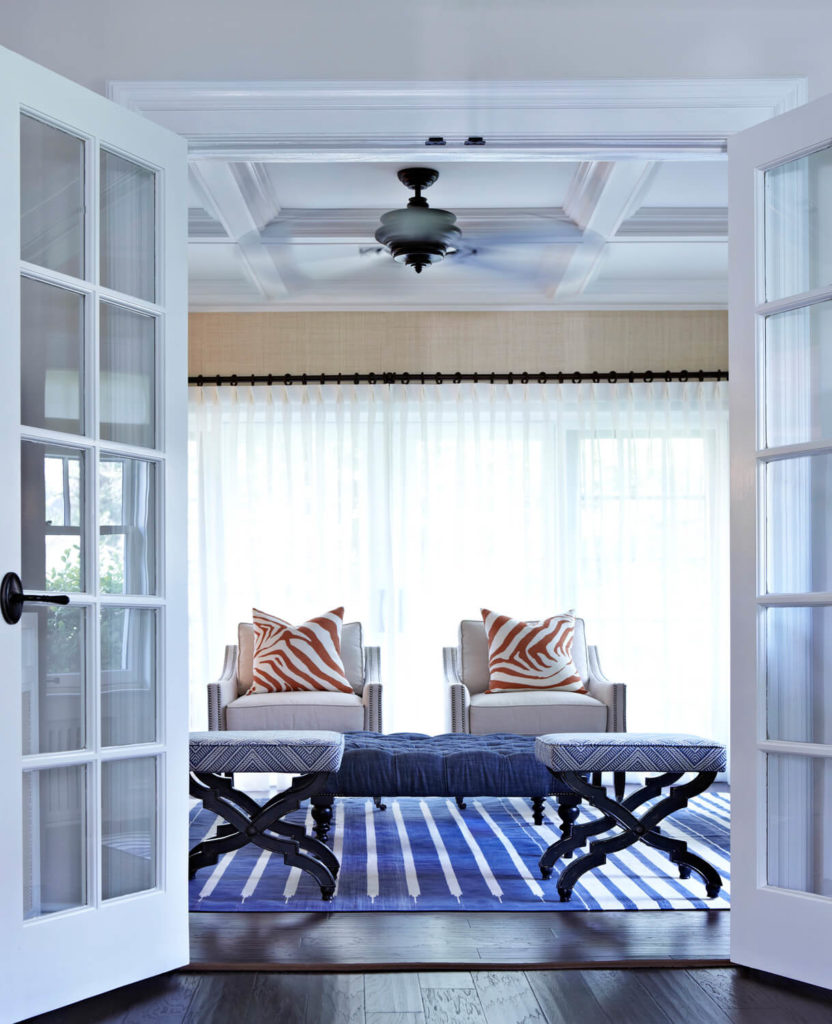 The view of the den from the French doors shows a nautical blue and white rug very similar to the rug in the foyer and orange zebra print throw pillows that match the curtains in the formal dining room.
