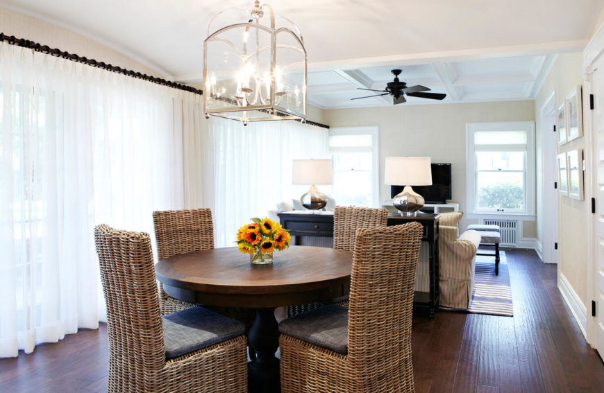 The informal dining table is surrounded by four wicker chairs. The light fixture is similar to the longer version hanging above the formal dining room. The vase of sunflowers matches the one in the entryway.
