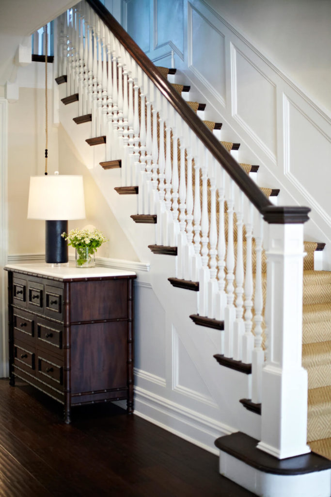 A closer look at the stairs and dresser shows the subtle geometric pattern of the carpet runner and the bamboo trim of the dresser. Wainscoting follows up the slope of the staircase, and along the side behind the dresser.