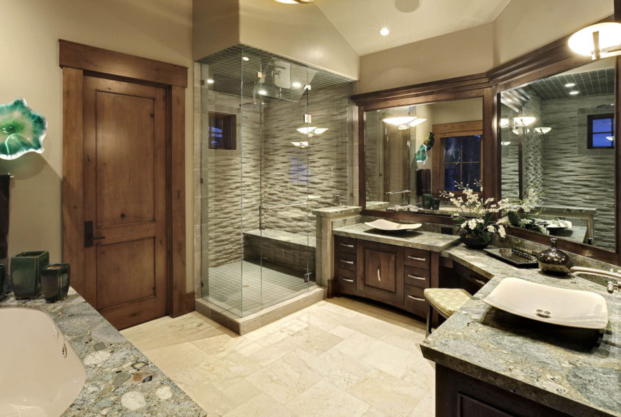 The lavish primary bathroom features a wraparound double vanity with vessel sinks over marble countertops and dark wood cabinetry. Large format mirrors and a glass enclosed shower add a bright and open sense.
