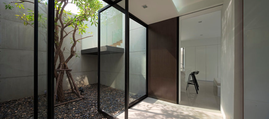 In this space, the full height glass panels open to a secluded garden area, with the glass wrapped staircase featuring at center.