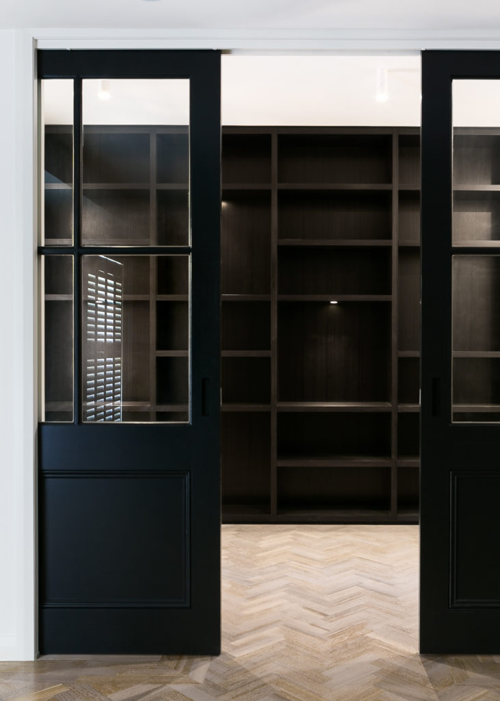 Here's another elaborate storage space, outside the main open area of the home. A pair of window-equipped pocket doors in dark timber open to reveal shelving mirroring that in the primary walk-in closet.