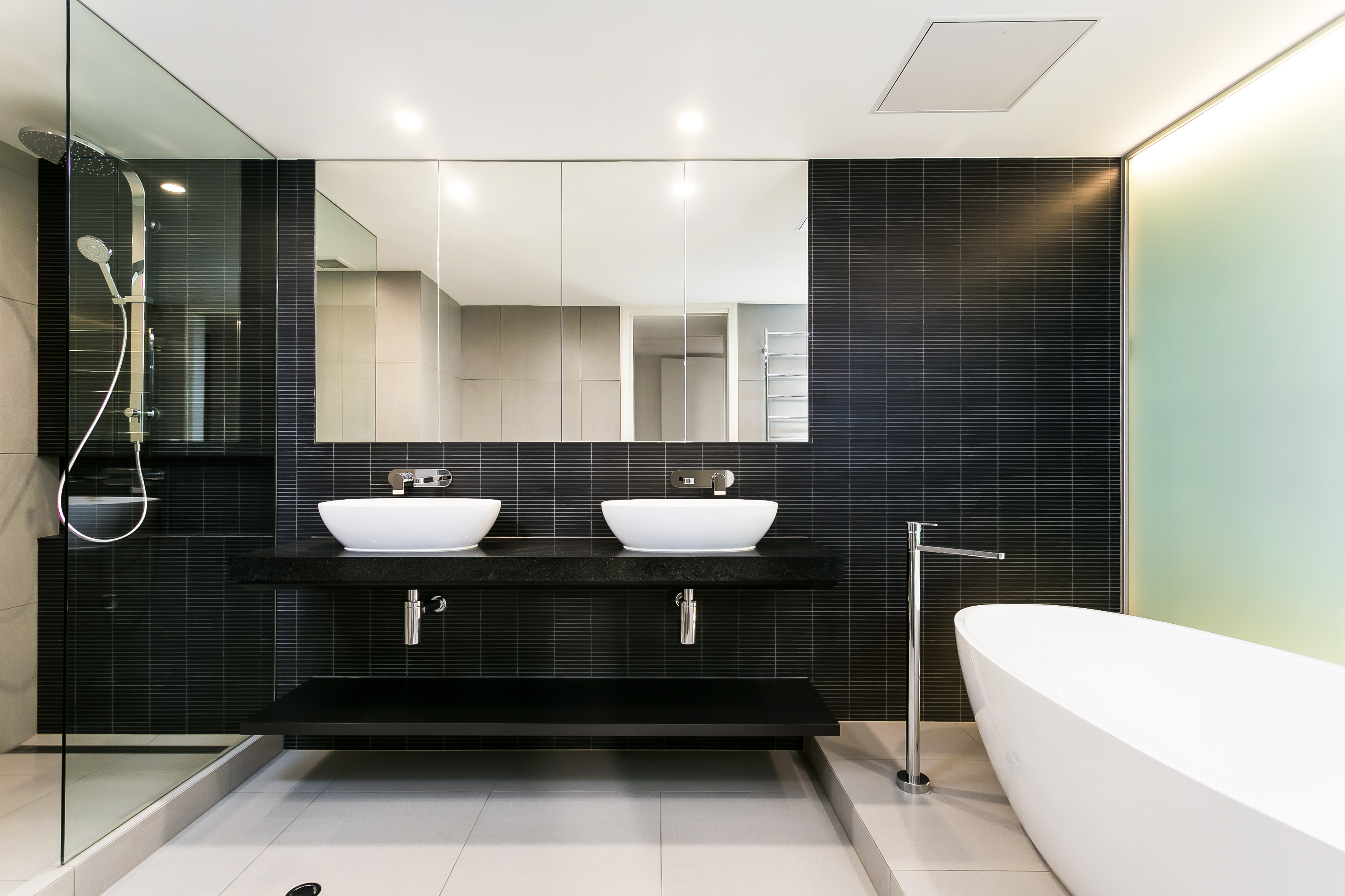 The primary bath hosts a high contrast mixture of tones, with black tiled wall over off-white large format beige floor tiling, plus white pedestal tub and vessel sinks. The floating black vanity hangs next to a large glass enclosed shower.