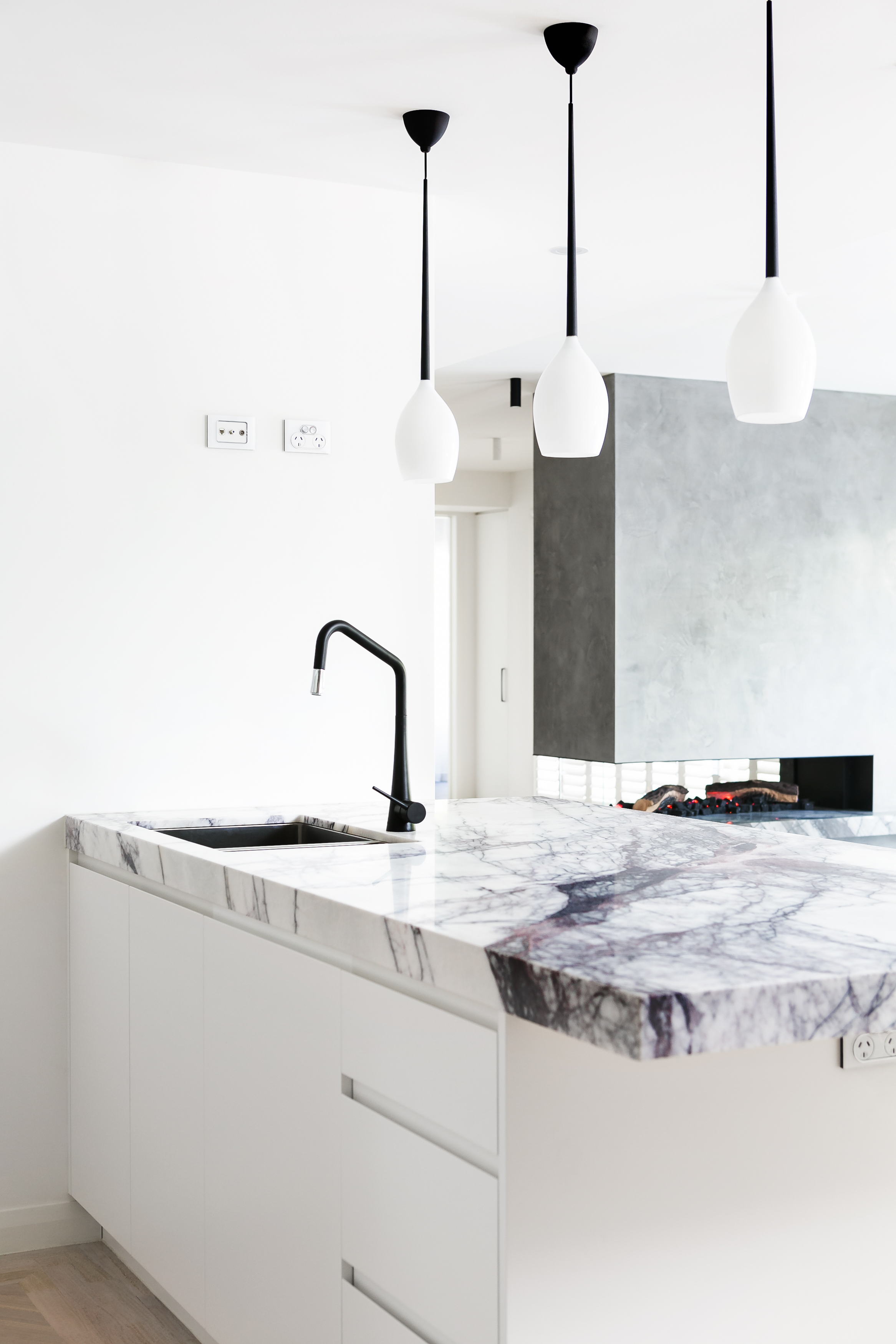 The granite countertop and sink with black faucet stand below a trio of black stemmed, white shade pendant lamps. The custom open fireplace can be seen in background at right.