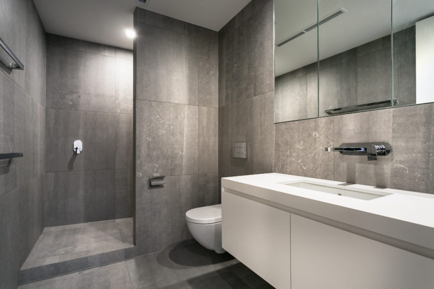 A second bathroom, awash in grey tile from floor to ceiling, features an open design shower and floating white vanity. Wall-mounted chrome faucet and frameless mirror add sparkling detail.