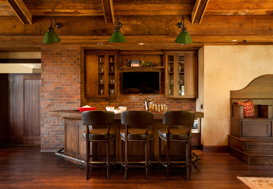 One of the home's entertainment spaces includes a game room with a home bar. The room has beautiful brick accents and hardwood floors