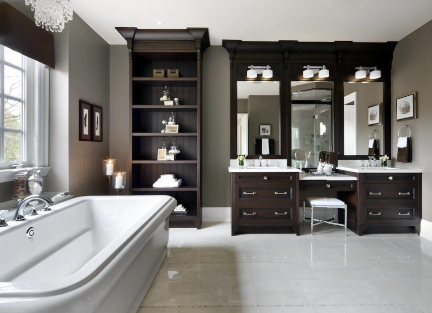 This primary bathroom features a freestanding shelf along with a powder desk in between two sinks. The deep soaking tub is lighted by a gorgeous chandelier.