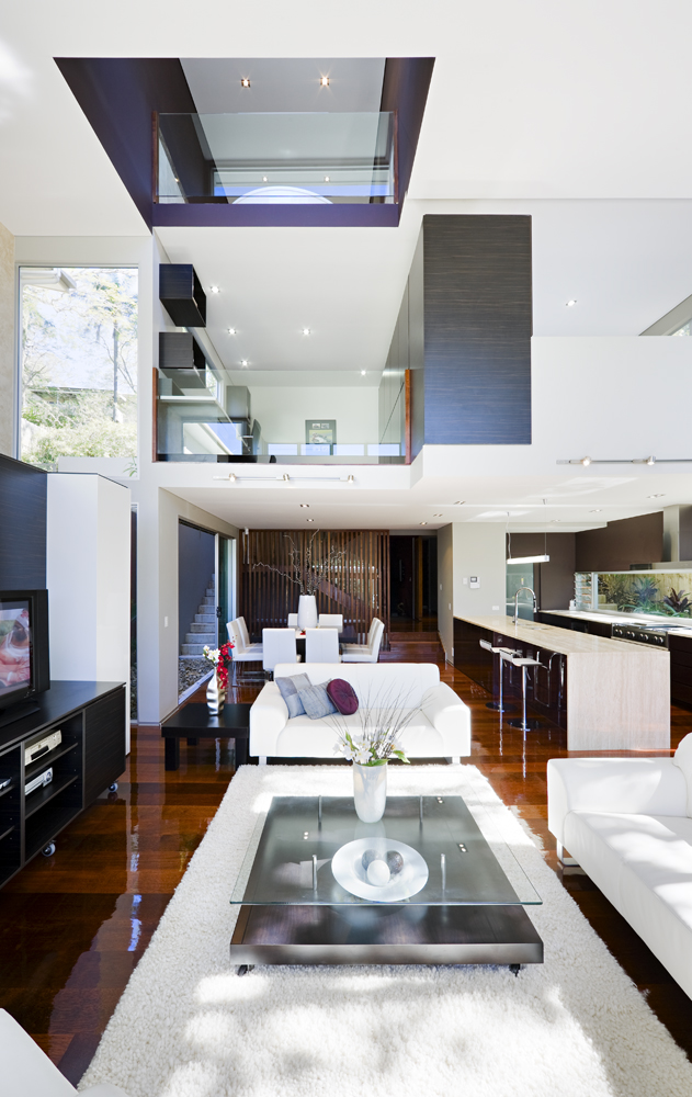 Moving indoors, we see a lush collection of contemporary furniture over glossy hardwood flooring. White surroundings highlight the ultra-modern details like glass safety walls defining the two levels overlooking this space.