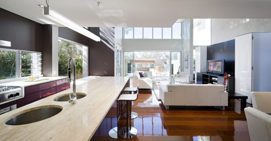 Looking back from the kitchen, we see the array of white sofas and the black wall behind the television creating contrast, with retractible glass door panels and overhead windows illuminating the entire space. Lengthy marble countertop can be seen at left.