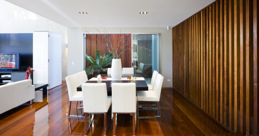 Defined within the larger open space by a large wood slat wall and placement beneath the upper level, the dining room features a large black table surrounded by metal frame, white leather upholstered chairs.